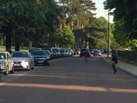 Plusieurs véhicules roulant sur la piste cyclable de Longchamp. Derrière le photographe de cet instant, des dizaines de cyclistes.